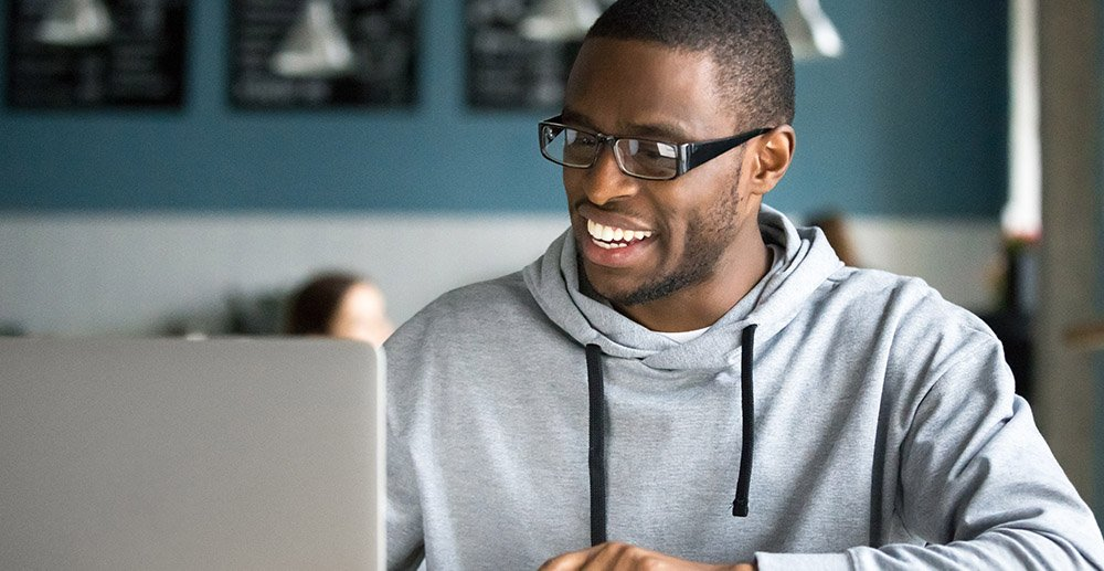 Smiling millennial african american casual man in glasses working on laptop in coffee shop wifi marketing analytics