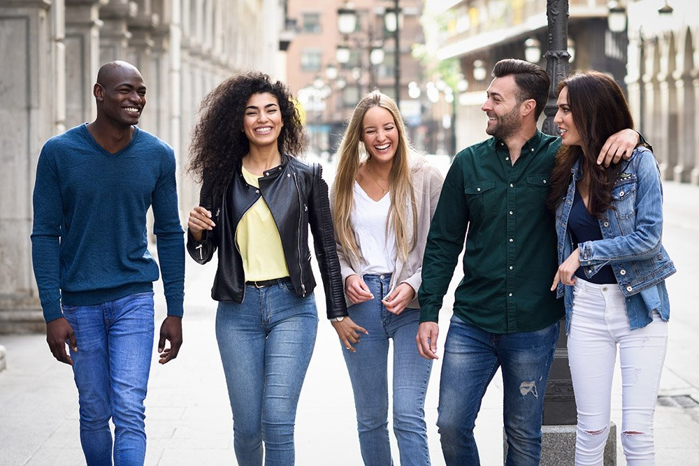 Multi-ethnic group of young people having fun together outdoors in urban background. group of people walking together