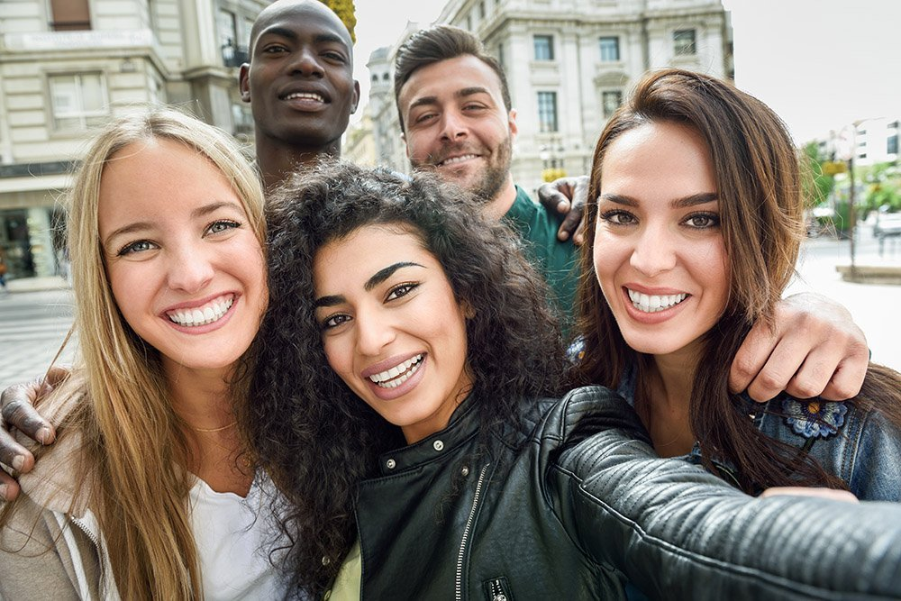 Multiracial group of friends taking selfie in a urban street.