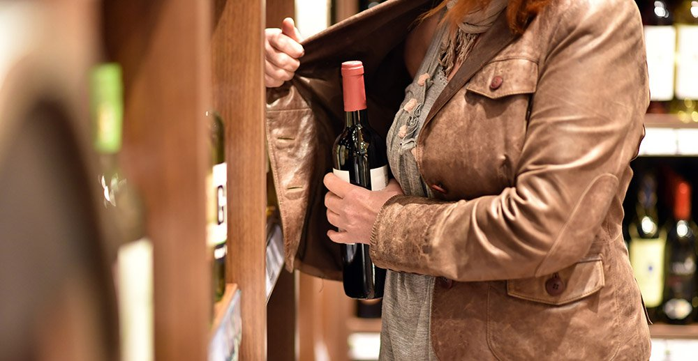woman stealing wine at store retail theft