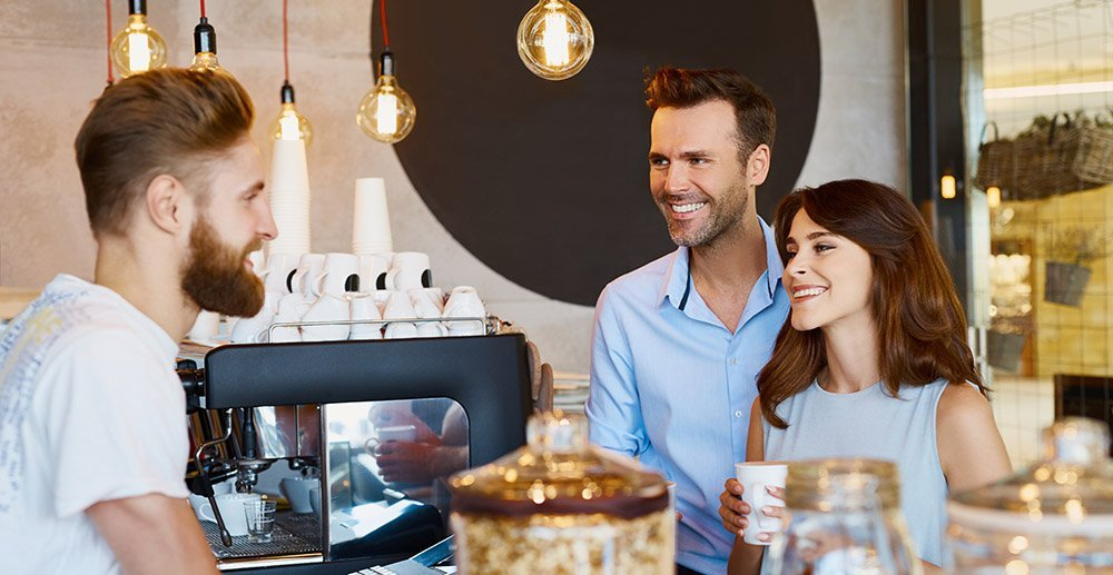 Couple at cafe talking barista, buying coffee customer engagement ideas