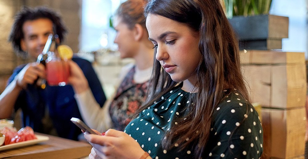 woman with smartphone and friends at restaurant how to improve text messaging