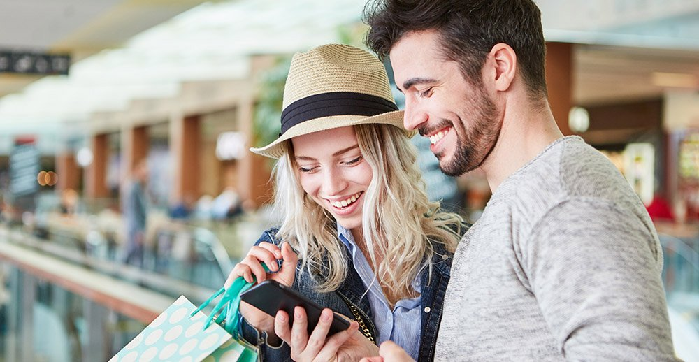 Couple shopping uses smartphone app customer engagement through social media