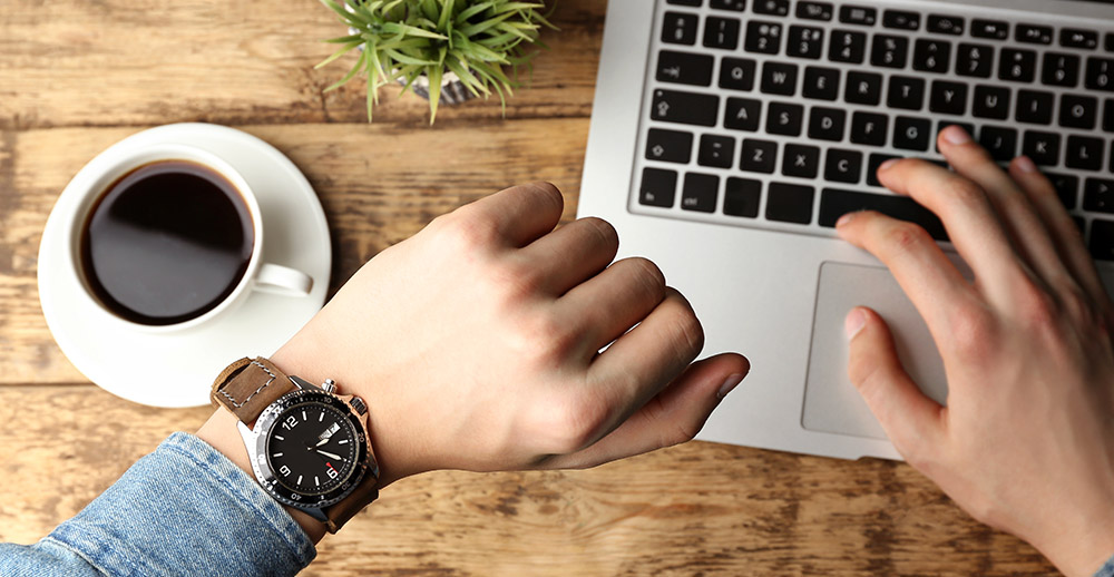 Hands of young man looking at watch while working with laptop employee time tracking software