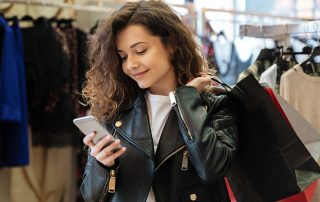 Cheerful curly young lady chatting by phone
