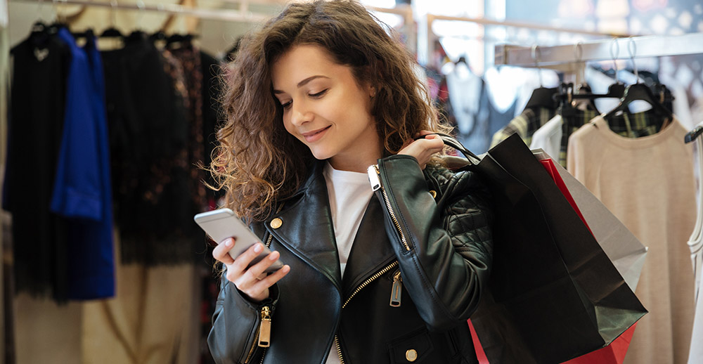 Cheerful curly young lady chatting by phone a guide to sms marketing