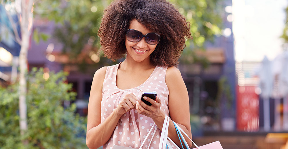 Smiling woman using her phone outdoors while shopping sms marketing strategy