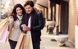 Shopping together. Millennial couple using smartphone outdoors