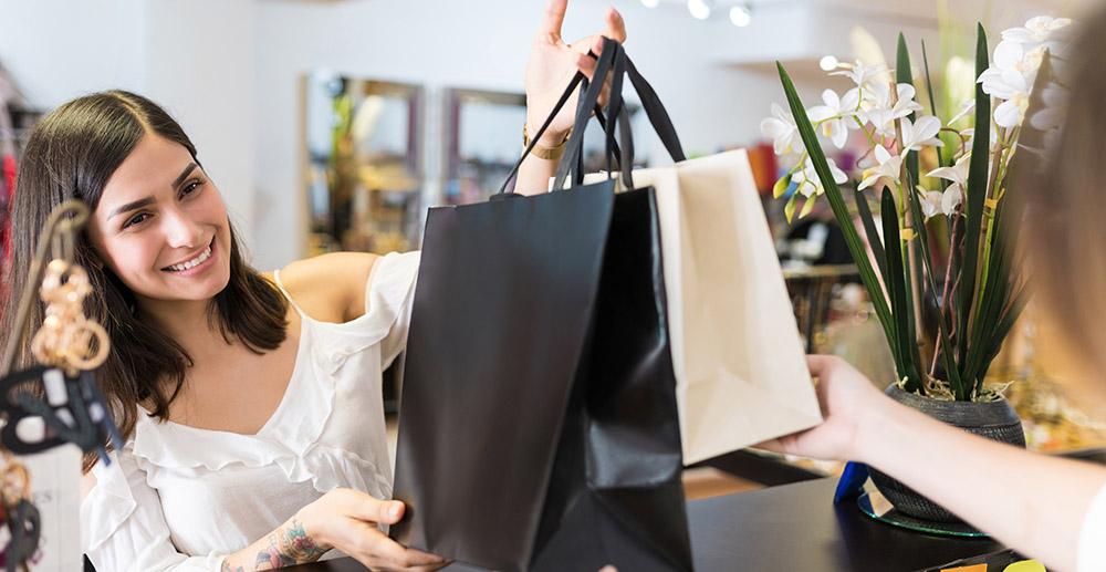 Customer Looking At Clerk Giving Apparel cross selling strategies