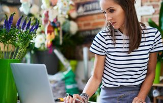 Portrait of young florist looking at client orders on laptop and notebook